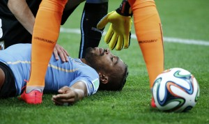 Uruguay's Pereira lies injured on the pitch after being hit in the face by England's Sterling during their 2014 World Cup Group D soccer match in Sao Paulo